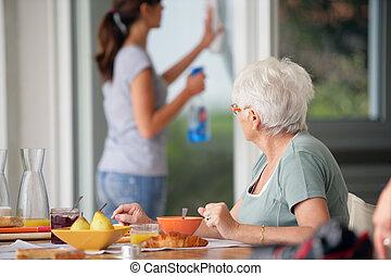 mulher sênior, tendo, pequeno almoço, com, cautela casa, em, a, fundo