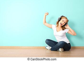 mulher, sala, parede, fones, jovem, escutar música, em branco, feliz