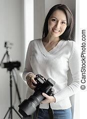 mulher segura, câmera, fotografia, hobby., ficar, dela, middle-aged, estúdio, bonito