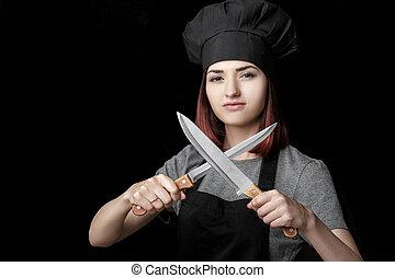 mulher, segura, foco, jovem, uniforme, cozinheiro, experiência., pretas, atraente, facas, dois