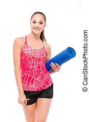 mulher segura, tapete, sorrindo, condicão física, ioga
