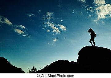 mulher, silueta, em, pôr do sol, em, montanhas