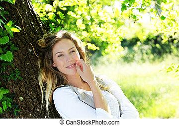 mulher sorridente, árvore, loura, inclinar-se
