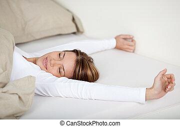 mulher sorridente, cama, esticar
