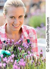 mulher sorridente, com, flor roxa, centro jardim