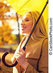 mulher sorridente, com, guarda-chuva, em, outono, parque
