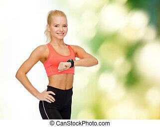 mulher sorridente, com, monitor taxa coração, ligado, mão