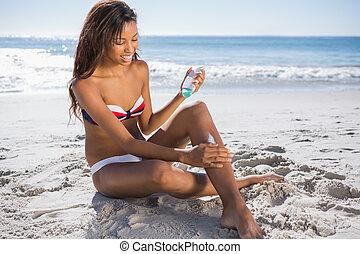 mulher sorridente, em, biquíni, aplicando, creme sol, ligado, dela, perna