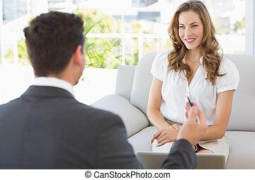 mulher sorridente, em, reunião, com, um, financeiro, conselheiro