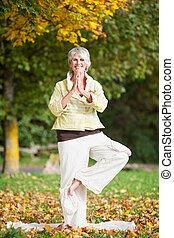 mulher sorridente, estar um pé, enquanto, fazendo, ioga