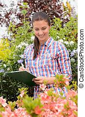 mulher sorridente, fazendo, inventário, em, centro jardim