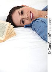 mulher sorridente, livro, cama
