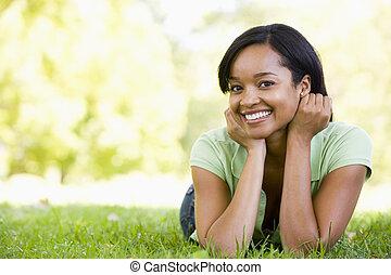 mulher sorridente, mentindo, ao ar livre