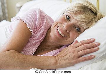 mulher sorridente, mentindo, cama