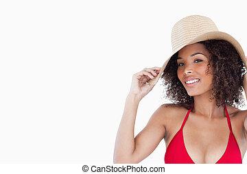 mulher sorridente, olhando câmera, enquanto, segurando, dela, chapéu palha