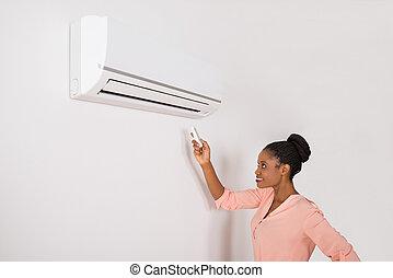 mulher sorridente, operando, condicionador ar