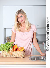 mulher sorridente, segurando, cesta, de, alimento orgânico