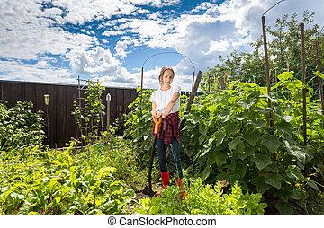 mulher sorridente, trabalhando, em, quintal, jardim, em, luminoso, dia ensolarado
