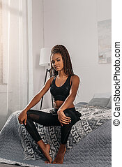 mulher, sportswear, cama, sentando