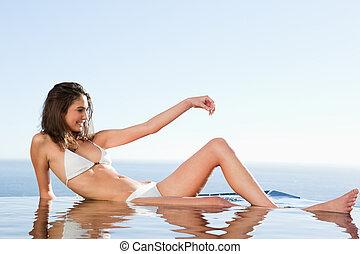mulher sunbathing, ligado, piscina, borda