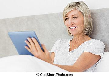 mulher, tabuleta, cama, maduras, digital, usando