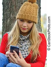mulher, texting, parque, jovem, outono, trendy