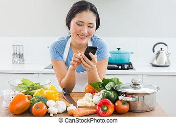 mulher, texto, legumes, frente, messaging, sorrindo, cozinha