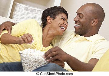 mulher, thirties, sentando, filme lar, par, observar, americano, junto, seu, rir, africano, pipoca, comer, homem, feliz