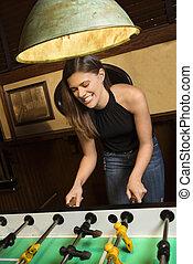 mulher, tocando, jovem, foosball.