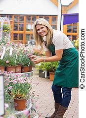 mulher, trabalhando, em, centro jardim, verificar, a, plantas