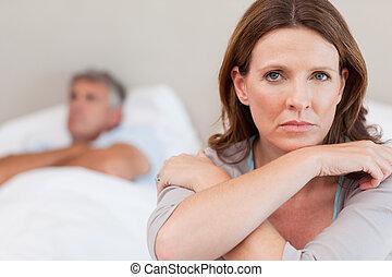 mulher triste, cama, com, marido, em, fundo