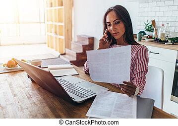 mulher usa computador portátil, e, falando telefone móvel, em, cozinha