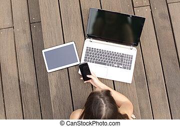 mulher, usando, múltiplo, dispositivos, telefone, laptop, e, tabuleta