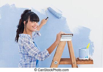 mulher, usando, pintar rolo, pintar, parede, e, sorrindo, câmera