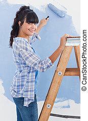 mulher, usando, pintar rolo, sorrindo, câmera