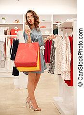mulher, usando, smartphone, enquanto, olhando, roupas