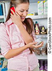 mulher usando telefone móvel, enquanto, olhar, produto