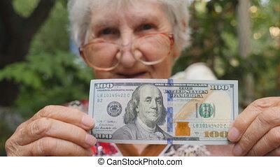 mulher velha, em, óculos, mostrando, cem contas dólar, em,...