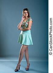 mulher, vestido, em, vestido verde, sobre, azul, cinzento, fundo