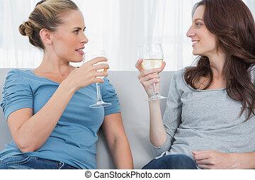 mulheres, clinking, seu, copos de vinho, enquanto, sentar-se sofa