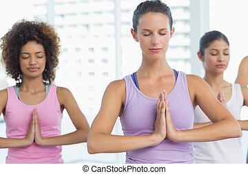 mulheres, em, meditação, pose, com, olhos fecharam, em, condicão física, estúdio