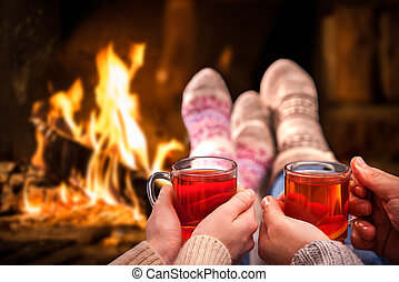 Couple relaxing with mulled wine at romantic fireplace on winter evening