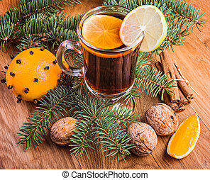 Mulled wine for winter and Christmas with spices and orange and walnuts on wooden table