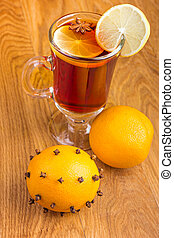 Mulled wine for winter and Christmas with spices and orange on wooden table