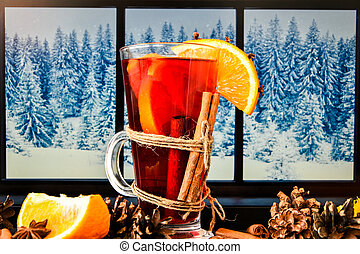 Mulled wine Hot christmas drink with spices on a windowsill, next to the window. Orange slices, cinnamon sticks, Pine cones.