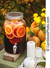 Mulled wine in a glass can on a festive autumn table for a family dinner in the garden.