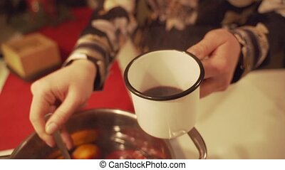 Mulled wine is poured into mugs on the table among Christmas...