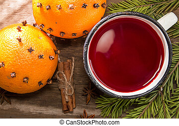 Mulled wine mug and two orange fruit decorated with carnation