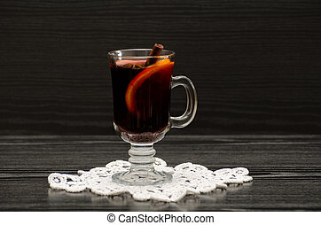 Mulled wine with spices on a lace napkin. Black wood background
