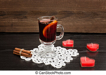 Mulled wine with spices on a lace napkin. Candles in the shape of a heart and cinnamon sticks. Wooden background